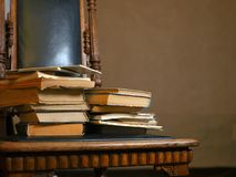 Stack of old books. Laid on the carved wooden vintage chair, vertical shot Royalty Free Stock Photos