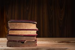 Stack of old books. On wooden table and background Royalty Free Stock Images