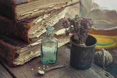 Stack of old books, vintage mortar of medicinal herbs, vial of h Royalty Free Stock Photos