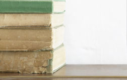 Stack of old books on wooden chest close up Stock Images