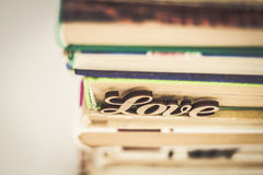 On a stack of old books wooden word love Stock Images