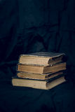 A stack of old books. A stack of old worn books on a background of dark fabric Royalty Free Stock Images
