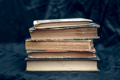 A stack of old books. A stack of old worn books on a background of dark fabric Stock Photo