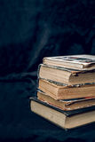 A stack of old books. A stack of old worn books on a background of dark fabric Stock Image
