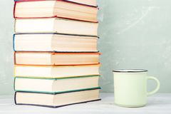 Stack of old color books and a cup of tea on a shelf and a green background. A stack of old color books and a cup of tea on a shelf and a green background Stock Photography