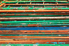 Stack of old dismantled metal ladders. Rusty steel pipes and flaking paint as industrial background Royalty Free Stock Images
