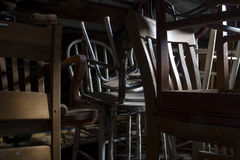Stack of old forgotten chairs in attic Stock Photos