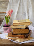 Stack of old hardback books and hyacinth on wooden background. Copy space. Stack of old hardback books and hyacinth on wooden background. Selective focus. Copy stock photo