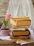 Stack of old hardback books and hyacinth on wooden background. Copy space. Stack of old hardback books and hyacinth on wooden background. Selective focus. Copy royalty free stock images