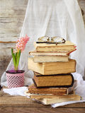 Stack of old hardback books and hyacinth on wooden background. Selective focus. Copy space stock photos