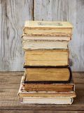 Stack of old hardback books on wooden background. Selective focus royalty free stock image