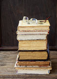 Stack of old hardback books on wooden background. Selective focus royalty free stock photography