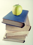 Stack of old hardcover books with green apple Royalty Free Stock Photography