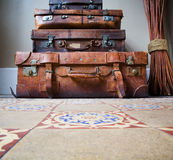 Stack of Old Leather Luggage on Tiled Floor. Copy space on floor Stock Image