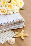 Stack of old letters and bouquet of pastel yellow roses Stock Photos