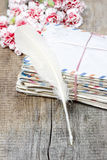Stack of old letters, feather pen and bouquet Stock Photography