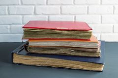 A stack of old photo albums against a brick wall royalty free stock photos