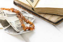 Stack of old photographs with amber necklace Stock Photos