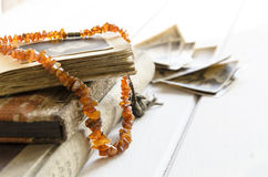 Stack of old photographs with amber necklace on photo album on white background Royalty Free Stock Image
