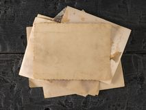 A stack of old photos on a black wooden table. The subject of family values. The view from the top royalty free stock photo