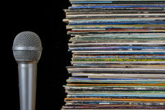 A stack of old records and microphone. Pile of old vinyl records and microphone on a black background Royalty Free Stock Image