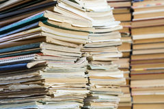 A stack of old school notebooks and a stack of textbooks or books.  stock photos
