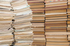 A stack of old school notebooks and a stack of textbooks or books.  stock images