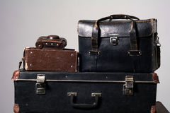 Stack of old shabby suitcase with a camera in bag Royalty Free Stock Photos
