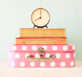 Stack of old suitcase, books and vintage clock over wooden table. retro style image Stock Photography