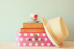 Stack of old suitcase, books and vintage cup of tea over table Stock Image
