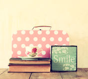 Stack of old suitcase, books and vintage tea cup over wooden table. retro style image Royalty Free Stock Image