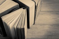 Stack of old and used hardback books or text books on wooden background. Monochrome stock images