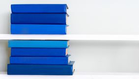 Stack of old vintage books on wooden shelf in university library. Stack of old vintage blue books on wooden shelf in university library for reading royalty free stock photography