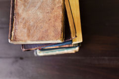 Stack of old vintage books on brown wooden background Royalty Free Stock Photo