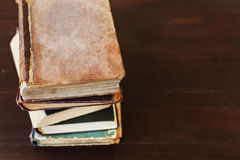 Stack of old vintage books on brown wooden background Stock Photo