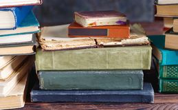 Stack of old vintage books on wooden shelf in university library. For reading stock photos