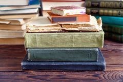 Stack of old vintage books on wooden shelf in university library. For reading stock images