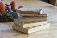Stack of old worn hardcover books. On a rustic wooden table alongside a candle decoration centerpiece in a conceptual image Royalty Free Stock Image