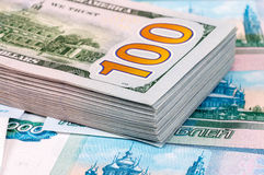 Stack of one hundred american dollar banknotes over roubles Royalty Free Stock Images