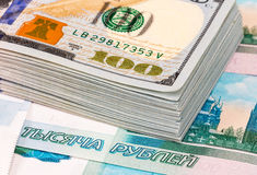 Stack of one hundred american dollar banknotes over roubles Royalty Free Stock Photo