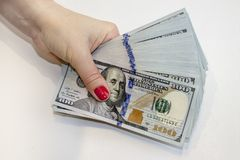 Stack of one hundred dollar banknotes in hand stock photography