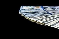Stack of one hundred dollar bills. Stack of cash money in hundred dollar banknotes. Heap of hundred dollar bills isolated on black Stock Photo