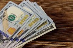 Stack of one hundred dollars bills on wooden desk. Stack of one hundred dollars bills on the wooden desk Stock Photo