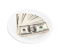 Stack of one hundred dollars on a plate Royalty Free Stock Photo