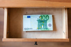 Stack of one hundred euro banknotes in drawer. Above view of stack of one hundred euro banknotes in drawer of nightstand Royalty Free Stock Images