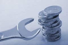 Stack of one pound coins and a spanner Royalty Free Stock Photos