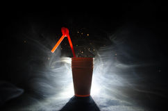 Stack of orange plastic cups with straw on dark background Stock Images