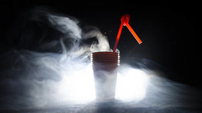Stack of orange plastic cups with straw on dark background Stock Photos