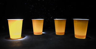 Stack of orange plastic cups with straw on dark background Royalty Free Stock Image