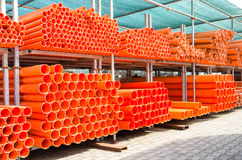Stack of orange pvc water pipes in abandoned industrial area Royalty Free Stock Photos